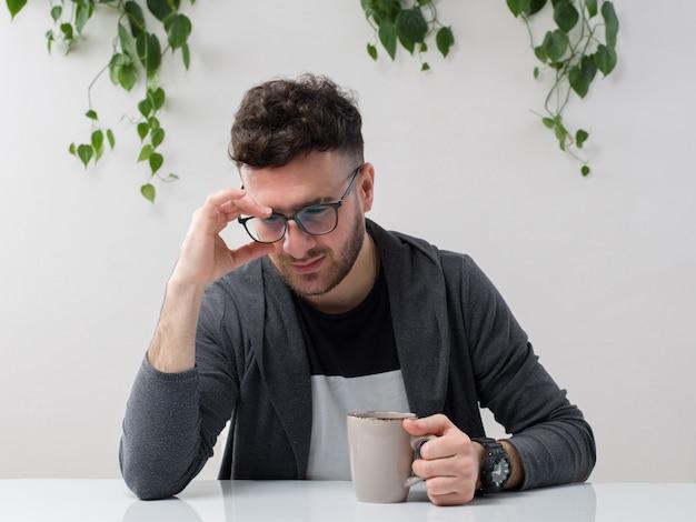 Молодой человек, сидящий в очках, смотрит серый пиджак вместе с растением на белом