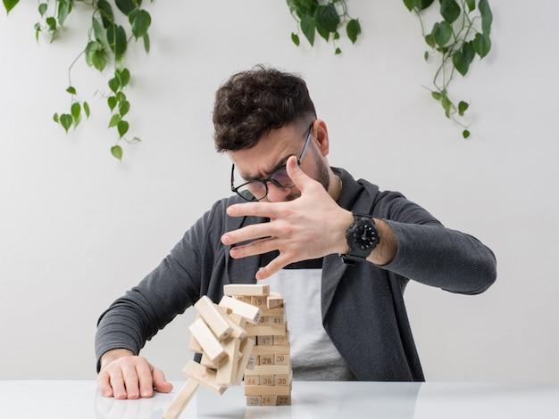 Молодой человек, сидящий в очках, наблюдает за тем, как серая куртка разрушает деревянное строение вместе с растением на белом