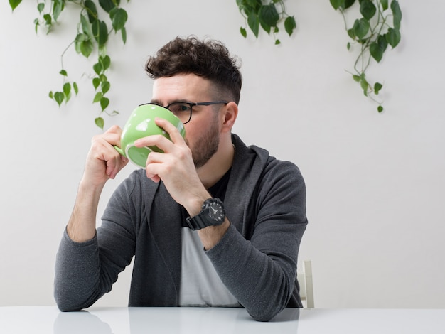 Молодой человек, сидящий в очках, смотрит, как серая куртка пьет его сок из зеленой чашки вместе с растением на белом