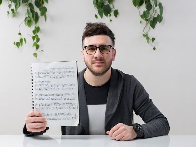 Молодой человек, сидящий в очках, смотрит на серый пиджак, держа тетрадь с нотами вместе с растением на белом