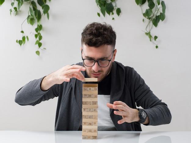 Молодой человек, сидящий в очках, смотрит, как серый пиджак играет с деревянными фигурами вместе с растением на белом