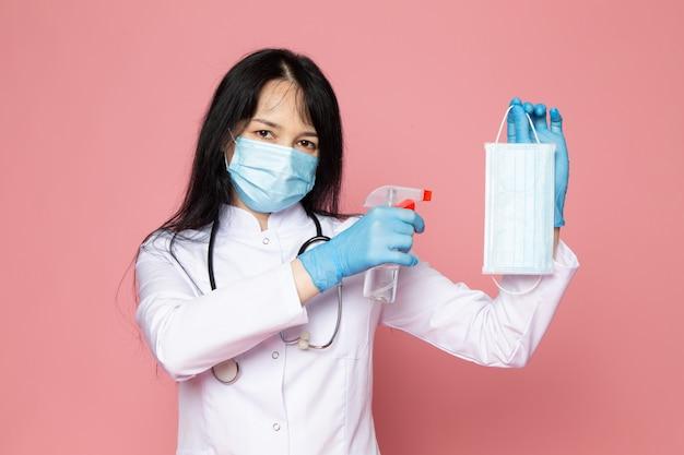 Молодая женщина в белом медицинском костюме синие перчатки голубая защитная маска со стетоскопом на розовом