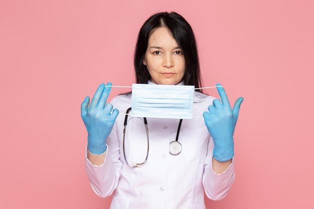 Молодая женщина в белом медицинском костюме синие перчатки со стетоскопом на розовом