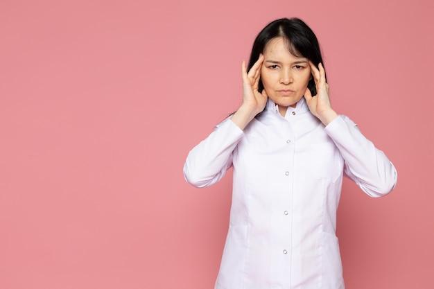 ピンクに激しい頭痛を持つ白い医療スーツの若い女性