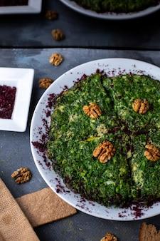 Вид сверху яйца с зеленью куку витамина богато вкусно с грецкими орехами на сером столе