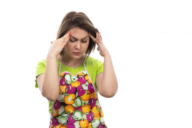 激しい頭痛に苦しんでいる緑のシャツのカラフルなケープの正面の若い美しい主婦