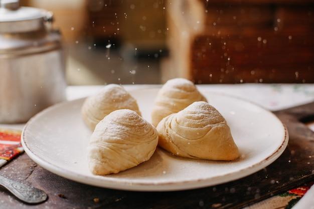 Знаменитая бадамбура со сладким фаршем из орехов, наполненная сахарной пудрой, вкусная внутри белой тарелки на коричневом деревянном столе в дневное время