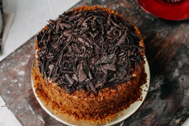 Торт сладкий вкусный вкусный коричневый с горячим чаем на сером столе
