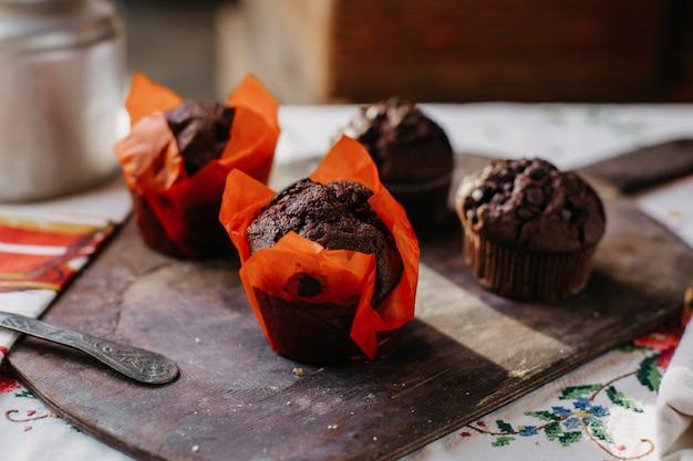 Шоколадные пирожные сладкие вкусные вкусные круглые с шоколадными укусами на коричневом деревянном столе в дневное время