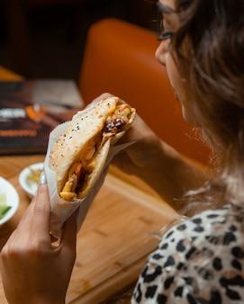 Женщина ест кебаб
