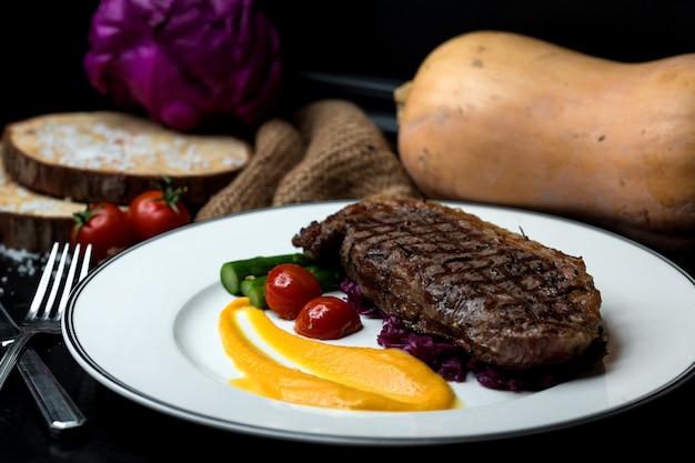 ビーフステーキに黄色のマッシュポテトと野菜を添えて