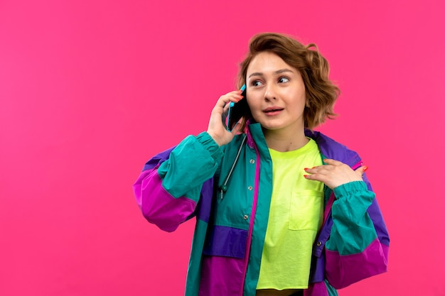 電話で話している酸性色のシャツ黒ズボンカラフルなジャケットの正面の若い美しい女性