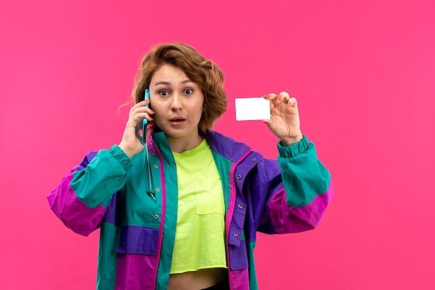 Вид спереди молодая красивая дама в кислотной рубашке, черные брюки, красочные пиджак, разговаривает по телефону