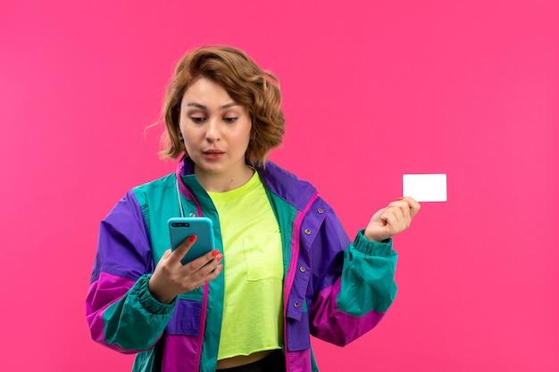 電話を使用して酸性色のシャツ黒ズボンカラフルなジャケットの正面の若い美しい女性