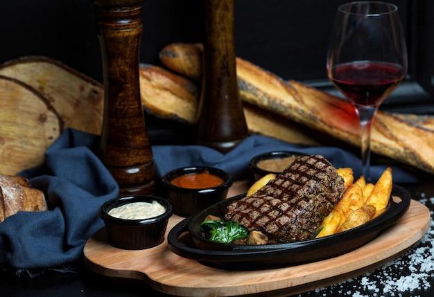 フライドポテト、マヨネーズ、マスタード、ケチャップを添えたビーフステーキ