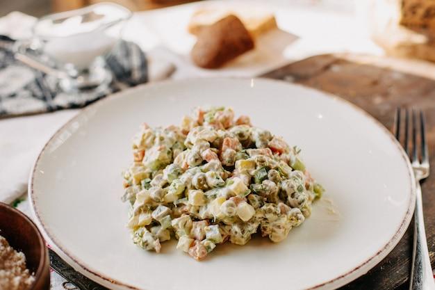 Майонез овощной салат соленый вкусный внутри белая тарелка вместе с вилкой для буханок хлеба в дневное время