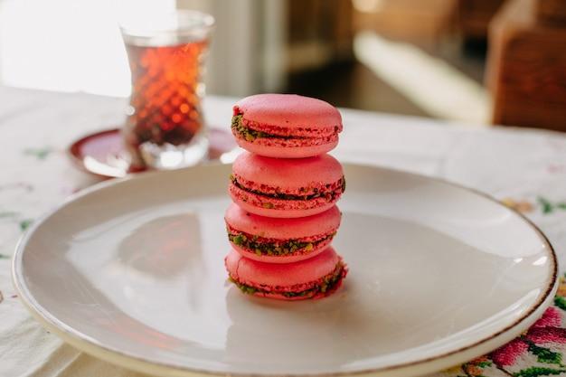 Розовые макероны сладкие вкусные круглые внутри белой тарелке вместе с горячим чаем в дневное время