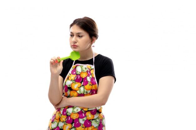 Вид спереди молодая красивая дама в черной рубашке и красочной накидке держит зеленый кухонный прибор, думая меланхолично