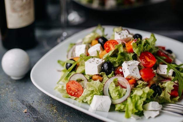 Греческий салат из нарезанных овощей с сыром, оливковым маслом и красным вином на сером