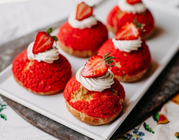白いプレート内のクリームスライスしたイチゴとおいしいおいしいイチゴの丸いケーキ