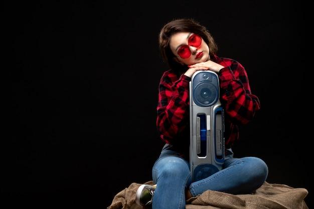テープレコーダーのかわいいポーズを保持している赤いサングラスの市松模様の赤黒シャツの正面の若い美しい女性