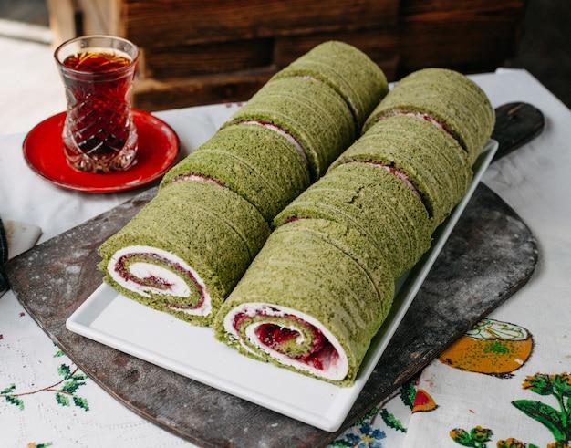 甘いロールスロイスは、白いプレートの中の熱いお茶のために内側に緑の粉末赤で設計されています