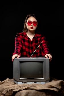 小さなテレビの近くの赤いサングラスの市松模様の赤黒シャツの正面の若い美しい女性