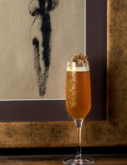 Бокал для шампанского с шампанским в нем, украшенный ломтиком сушеного лимона