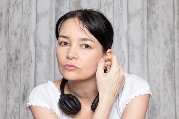 灰色の壁に黒のイヤホンで音楽を聴く白いシャツの若い女性