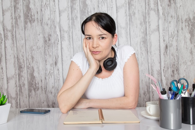 Девушка в белой рубашке показывает эмоции своими руками в черных наушниках на серой стене