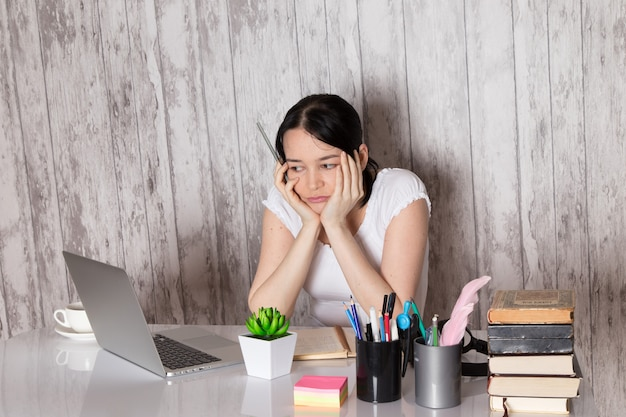 Молодая леди в белой футболке, используя серый ноутбук на столе чашка кофе завод ручки книги на серый