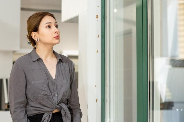 Вид спереди молодая красивая дама в серой рубашке и джинсах смотрит на что-то сосредоточенное на работе