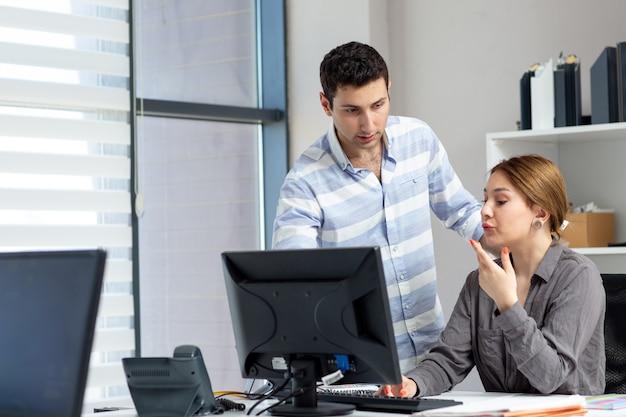 灰色のシャツの正面の若い美しい女性の話と昼間の建物の仕事の活動中にオフィス内の若い男と何かを議論