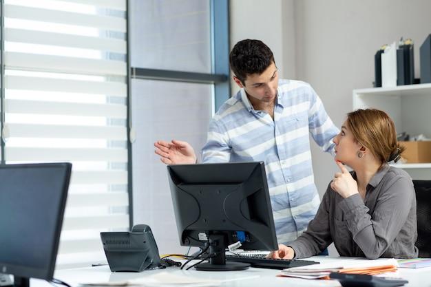Вид спереди молодая красивая дама в серой рубашке разговаривает и обсуждает что-то с молодым человеком в офисе во время дневного строительства