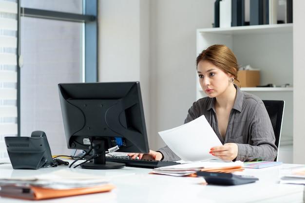 Вид спереди молодая красивая дама в серой рубашке работает на своем компьютере, сидя в своем офисе во время дневного строительства