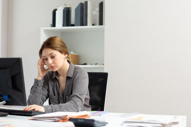 Вид спереди молодая красивая дама в серой рубашке работает с документами, используя свой компьютер, сидя в своем офисе, думая, волнуясь в дневное время, строя работу