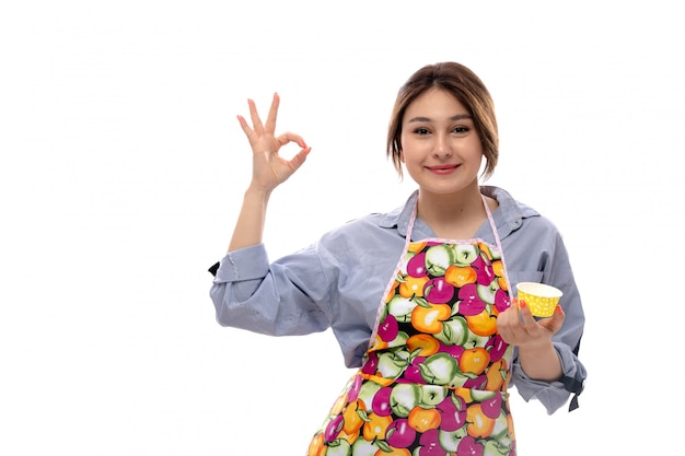 Вид спереди молодая красивая дама в светло-голубой рубашке и красочной накидке, держащей желтые кастрюли, счастливое улыбающееся выражение