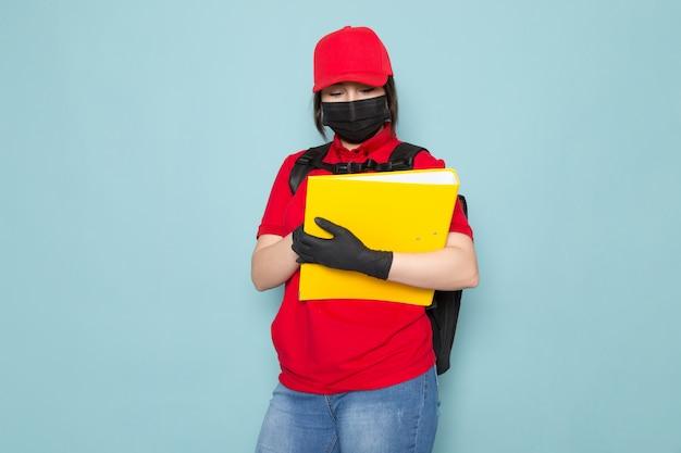 青のパッケージを保持している赤いポロ赤キャップ黒滅菌防護マスク黒バックパックの若い宅配便