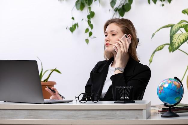 Вид спереди молодая красивая дама в белой рубашке и черной куртке, используя свой ноутбук перед столом, разговаривает по телефону с листьями висит