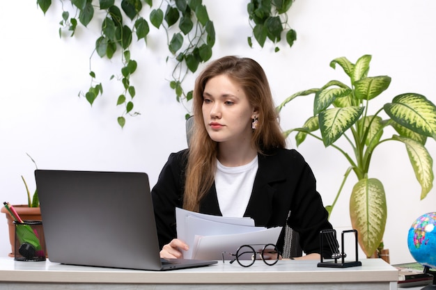 Вид спереди молодая красивая дама в белой рубашке и черной куртке работает с документами, используя свой ноутбук перед столом с листьями висит