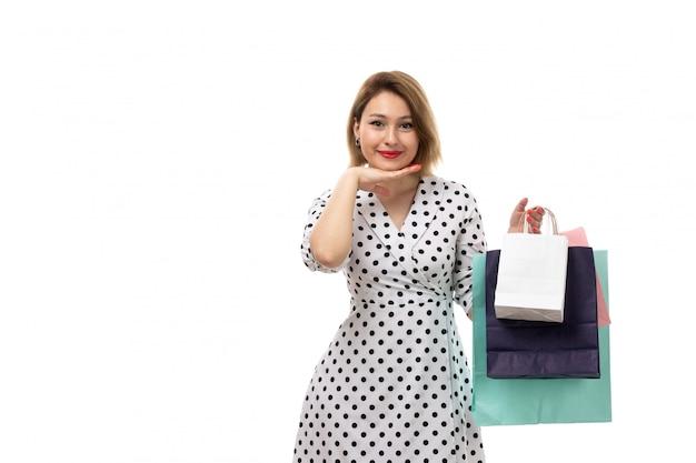 ショッピングパッケージを保持している笑顔の黒と白の水玉ドレスの正面の若い美しい女性