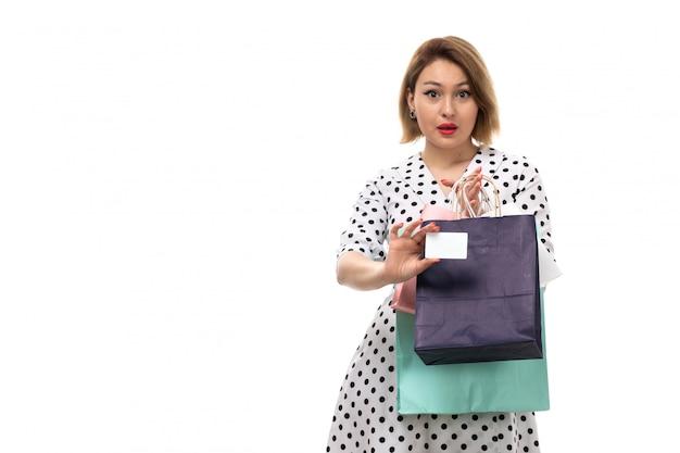 白いカードを見せて驚いたショッピングパッケージを保持している黒と白の水玉ドレスの正面の若い美しい女性