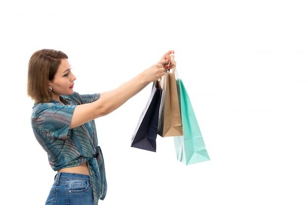 Вид спереди молодая красивая женщина в цветной блузке синих джинсах держит пакеты покупок