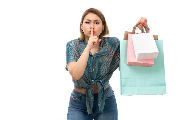 Вид спереди молодая красивая женщина в цветной блузке синих джинсах держит пакеты покупок, показывая знак молчания