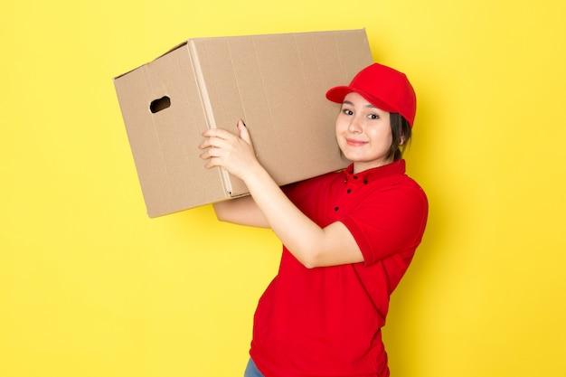 黄色に笑みを浮かべてパッケージを保持している赤いポロ赤い帽子の若い宅配便