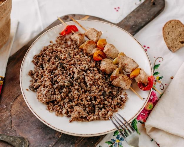 Вареная гречка вместе с жареными кусочками мяса на маленьких палочках внутри белых тарелок хлебные булочки на красочном салфетке в дневное время