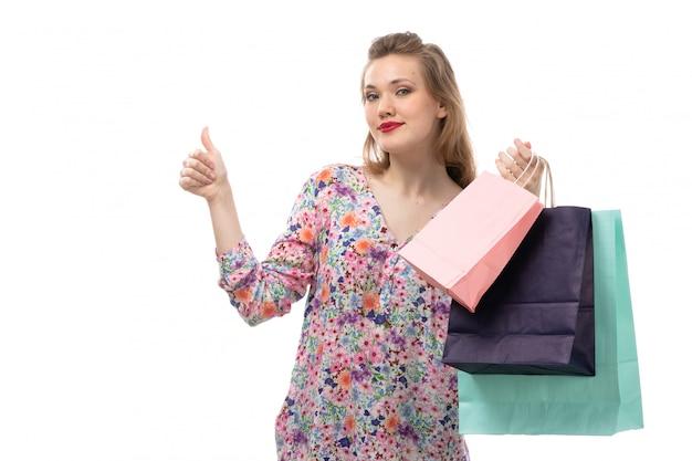 花の正面の若い美しい女性デザインのシャツとショッピングパッケージを保持している黒いズボン