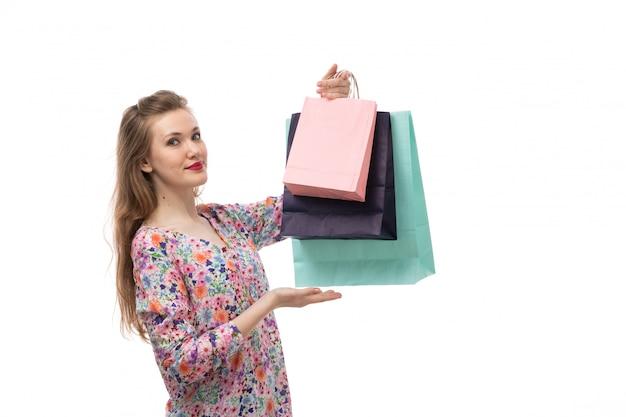 Вид спереди молодая красивая женщина в цветочной рубашке и черных брюках с пакетами для покупок