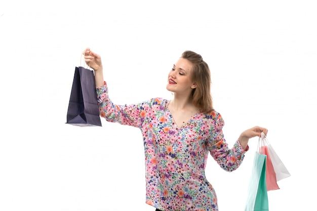 花の正面の若い美しい女性デザインのシャツとポーズのショッピングパッケージを保持している黒いズボン