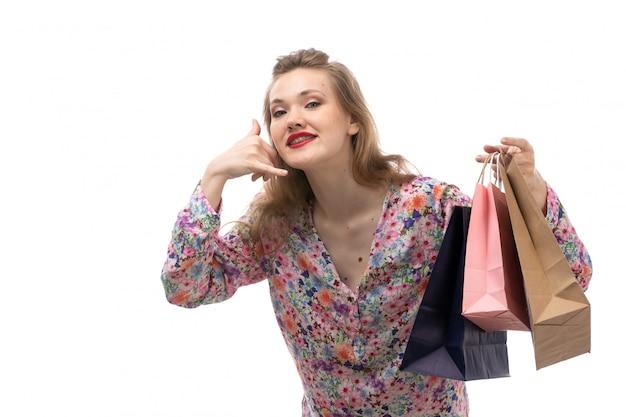 花の正面の若い美しい女性デザインのシャツと電話ジェスチャーを示すショッピングパッケージを保持している黒いズボン